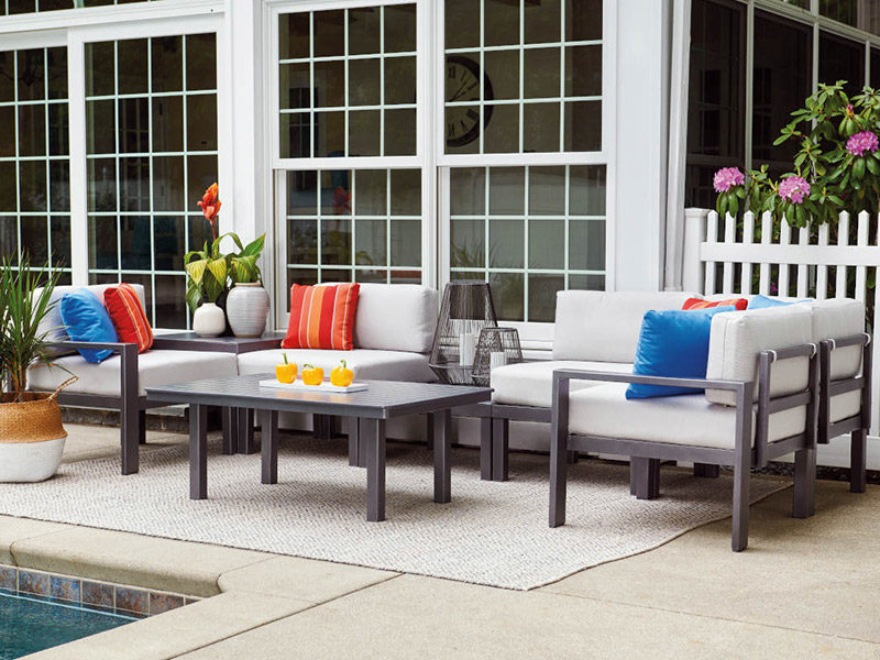 dark gray patio furniture with light gray cushions and a matching table on a tan outdoor rug next to an inground pool and white house